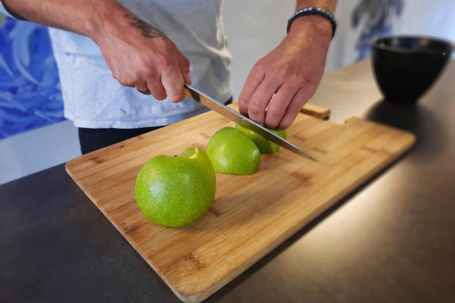 Eine Hand die ein Messer hält und eine Zweie hält eine Apfelspalte. Alles liegt auf einem Holzbrett.