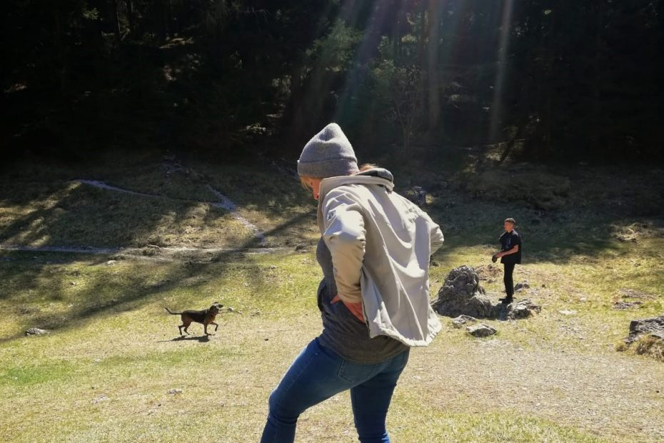 Eine Frau mit Jacke steht auf einer Wiese vor einem See.
