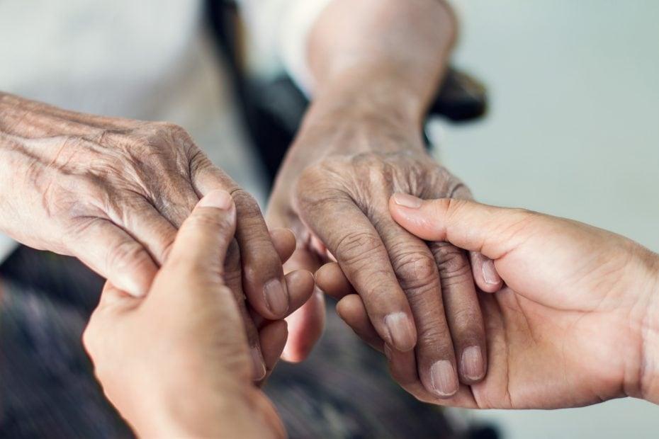 Zwei Menschen reichen sich die Hände. Ein jüngerer und ein älterer Mensch.