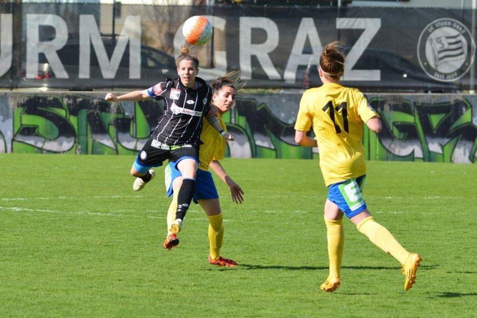 Drei Frauen auf einem Fußballfeld. Eine springt gerade in die Luft in Richtung Ball.