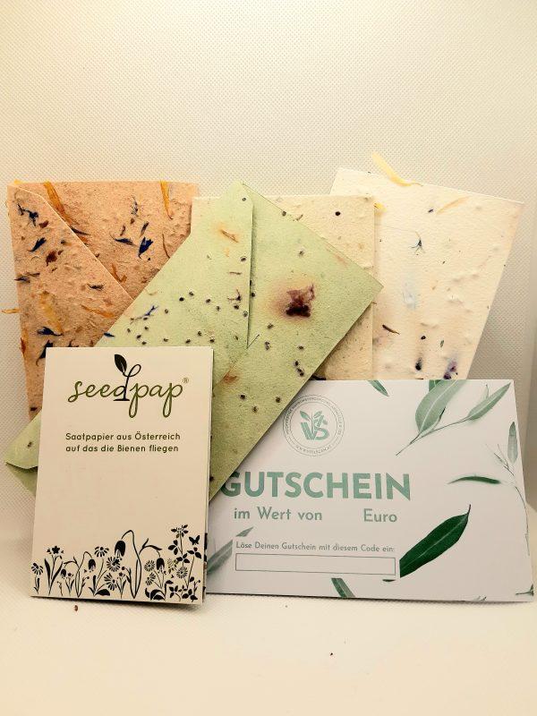 Gutscheine in grün und weiß. Dahinter Kuvert aus Saatgutpapier.