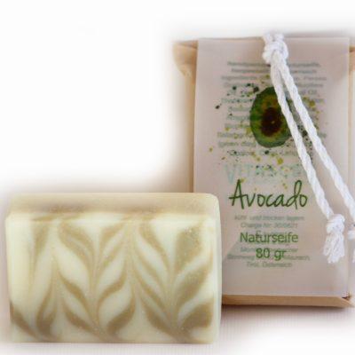 Weiße Verpackung mit einem selbstgemachten Etikett in Grün mit der Aufschrift Avocado. Ein Stück Seife steht vor dem Paket.