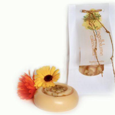 Runde Seife und zwei Ringelblumen. Im Hintergrund eine verpackte Seife in einem weißen Papier mit Sichtfenster.