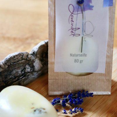 Eine Seife mit Lavendelblüten. Im Hintergrund die nachhaltige Verpackung mit Sichtfenster und dem Etikett mit geschwungener Aufschrift.